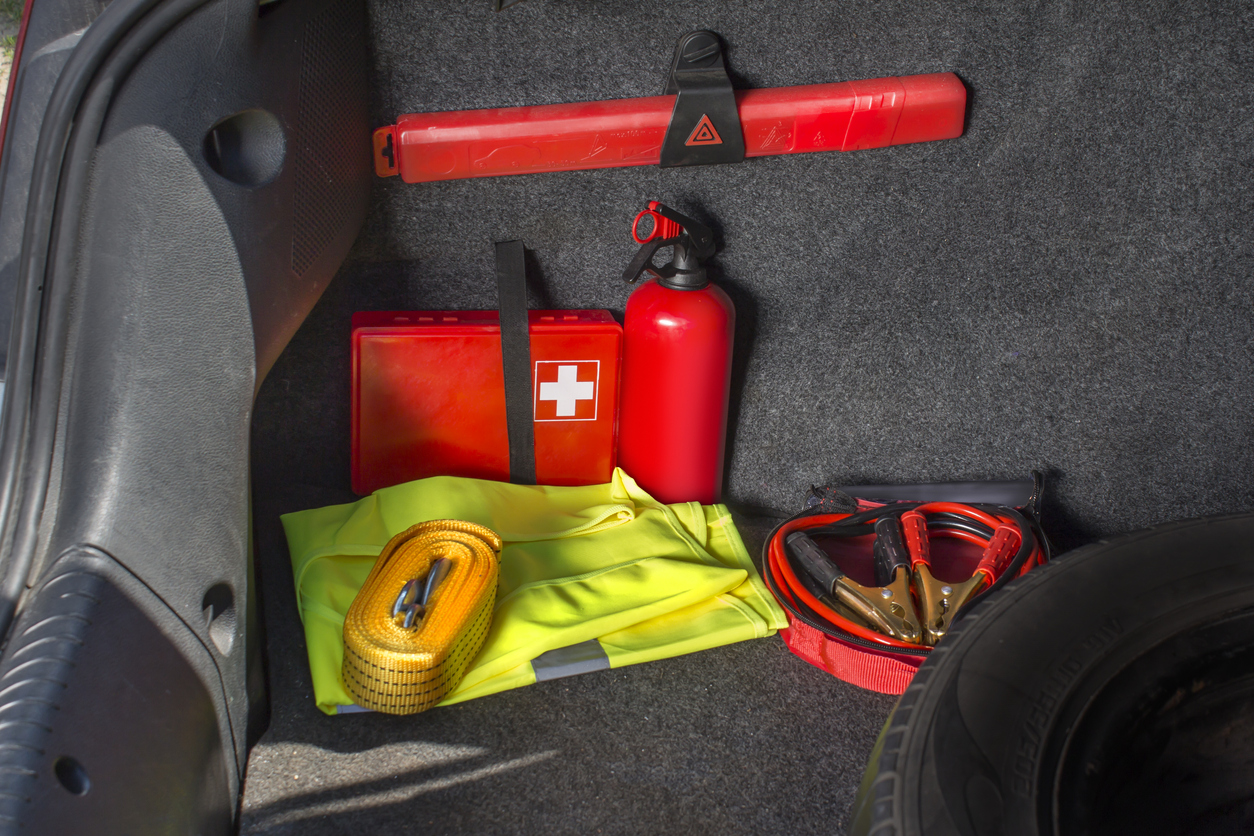 Car emergency kit and first aid kit neatly organized in a car trunk
