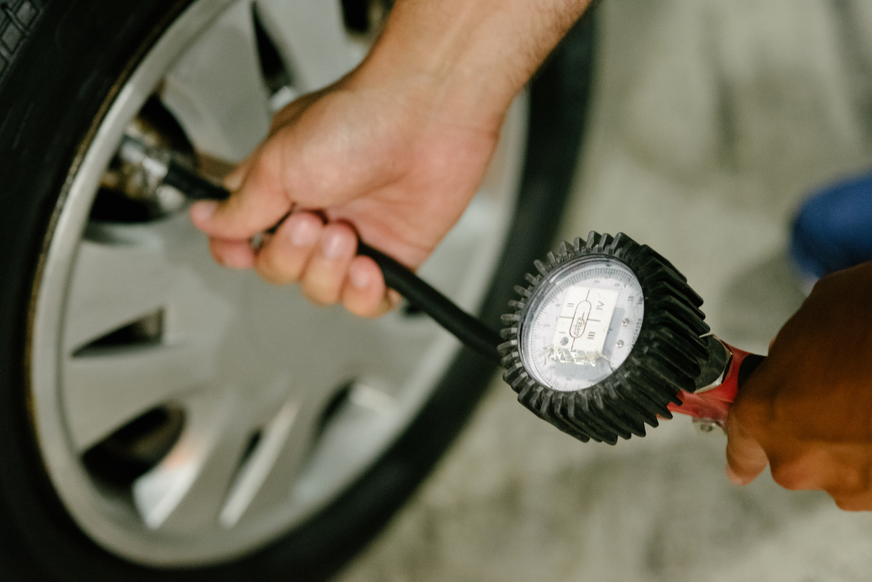 Car owner checking the air pressure in their tire while holding a flashlight