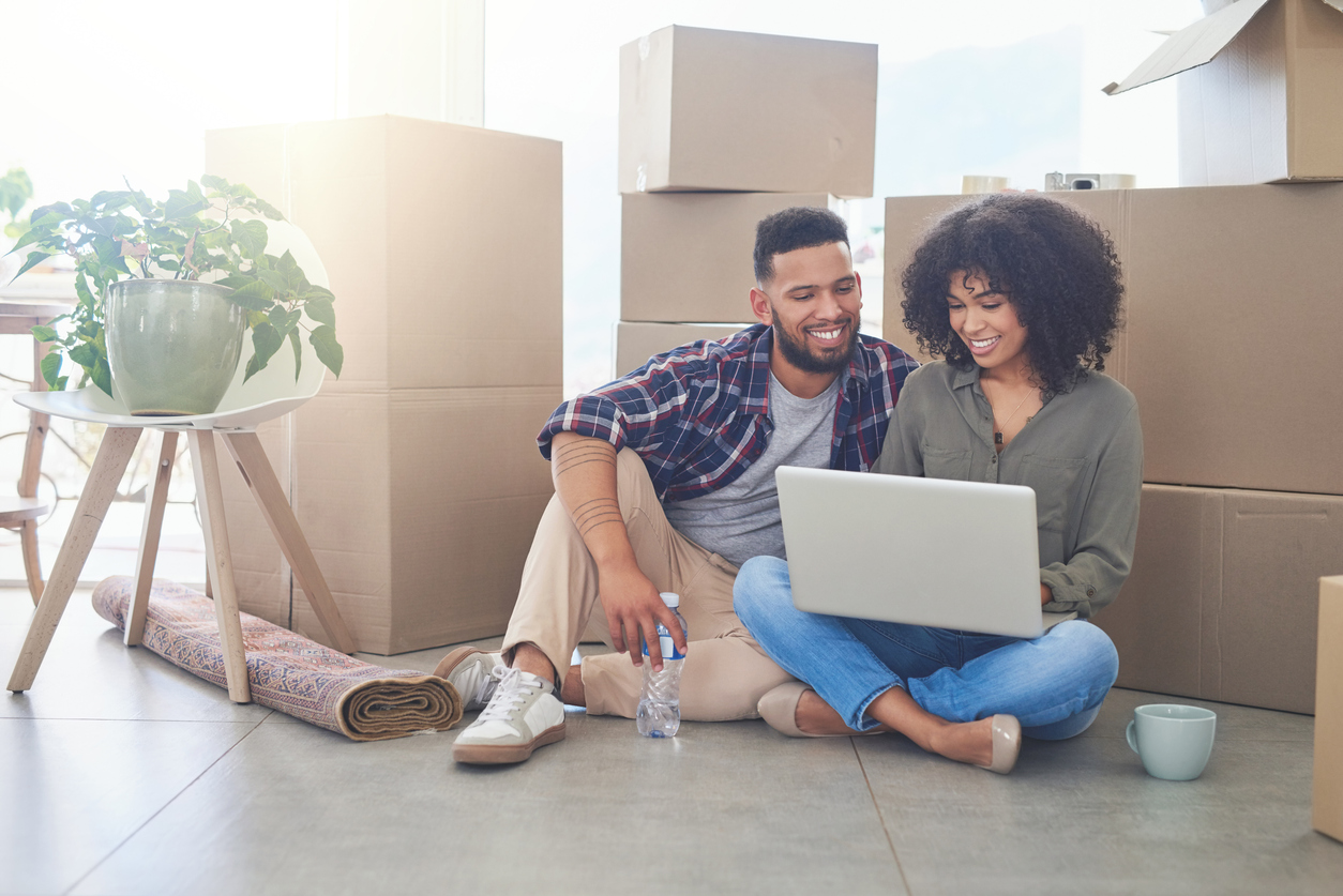 Couple researching storage unit insurance as they pack to move out