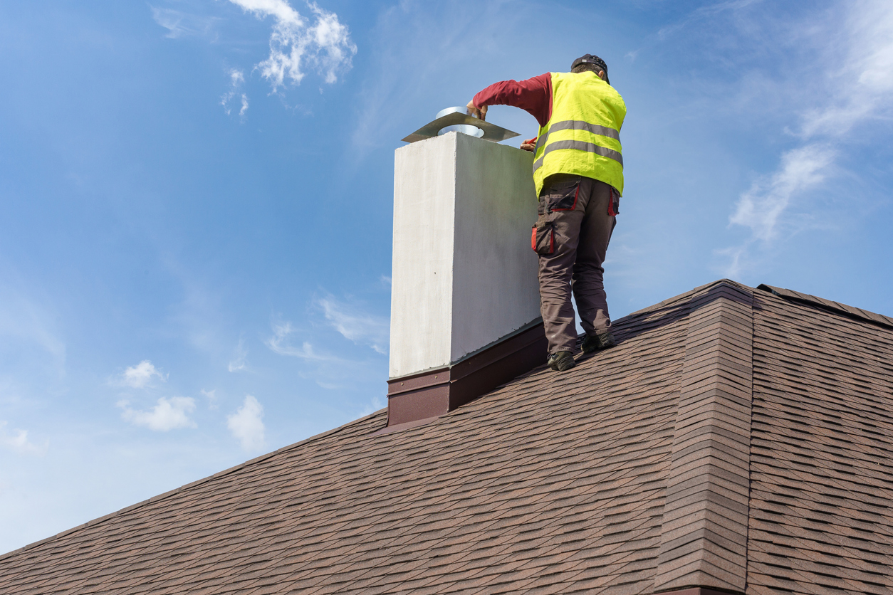 Man removing a chimney cap from his chimney