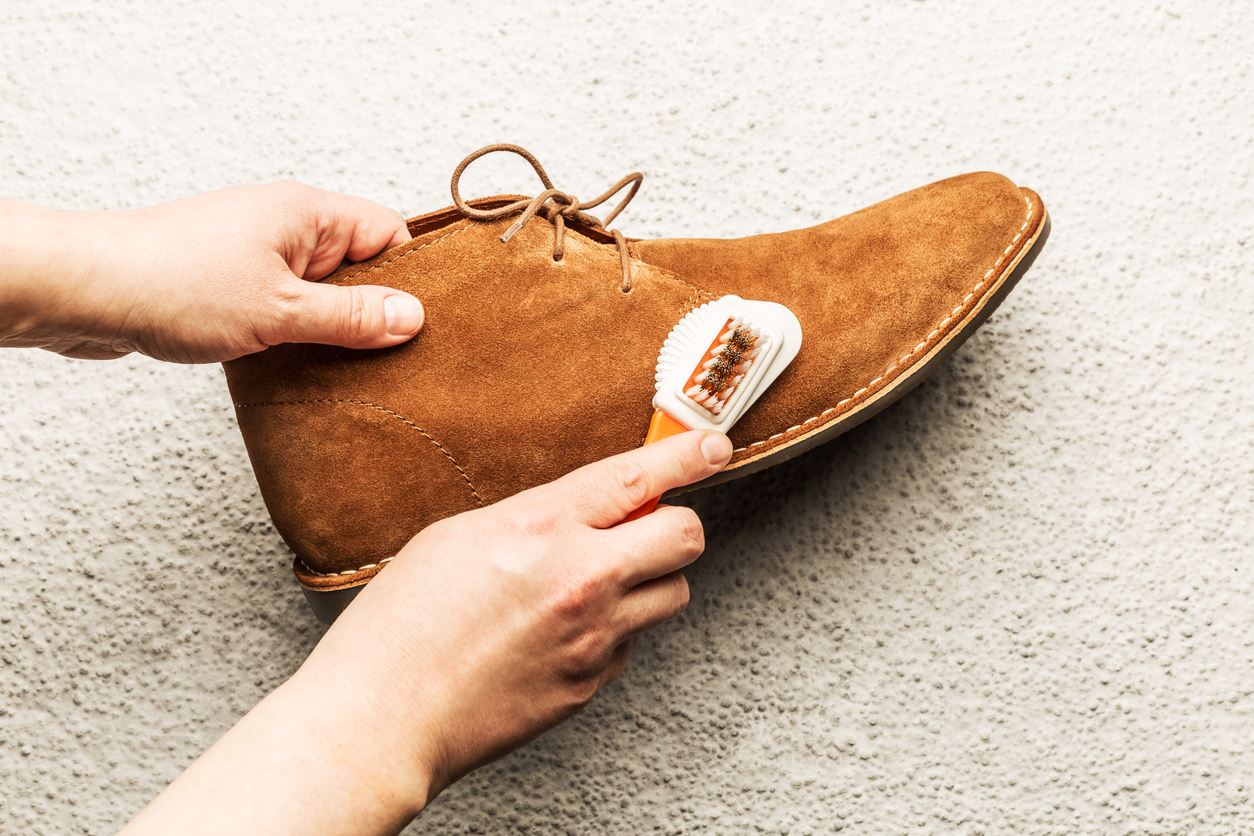 Someone gently scrubbing a leather boot with a soft-bristle brush and leather conditioner