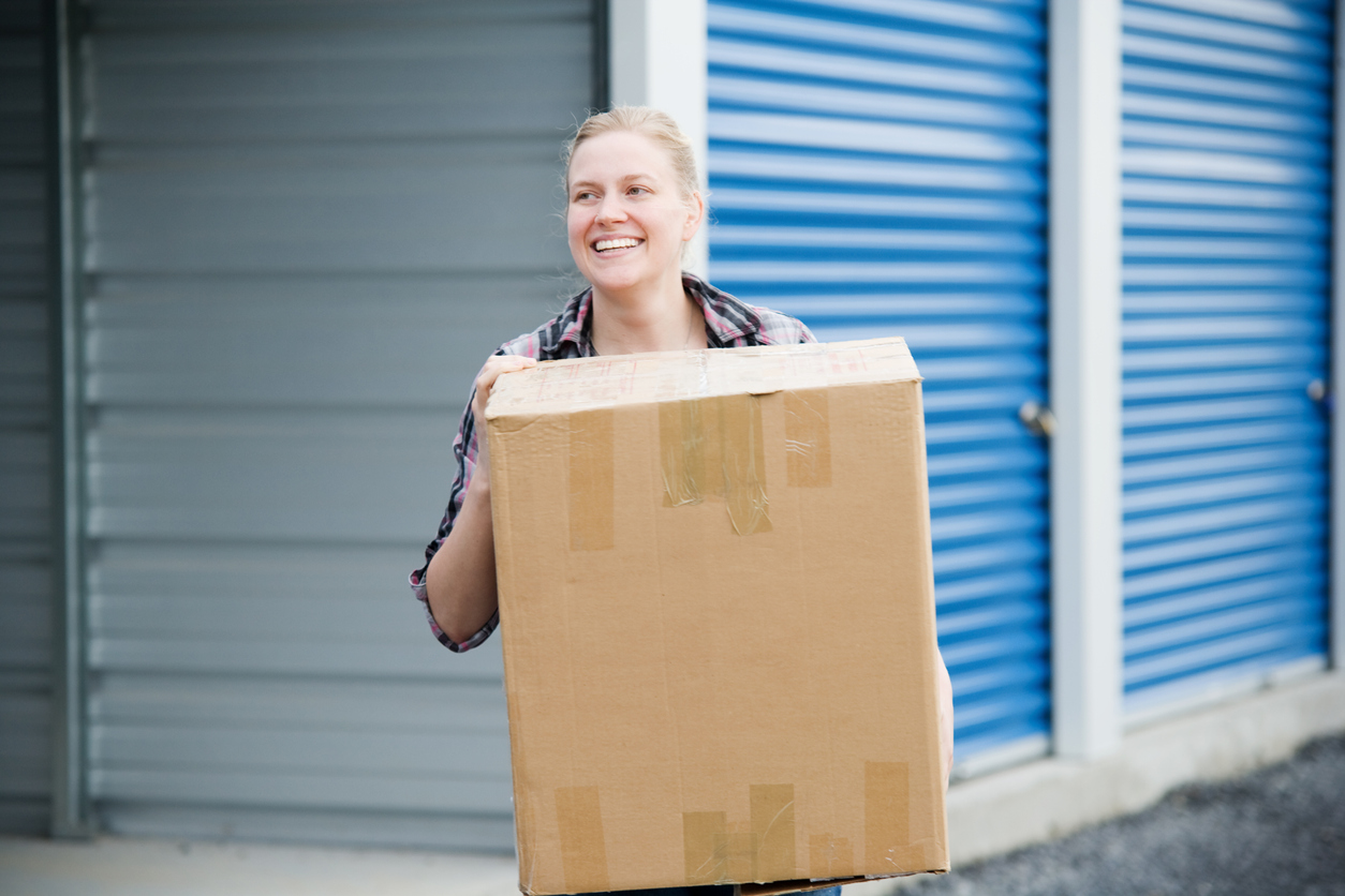 Woman carrying a box to a storage unit