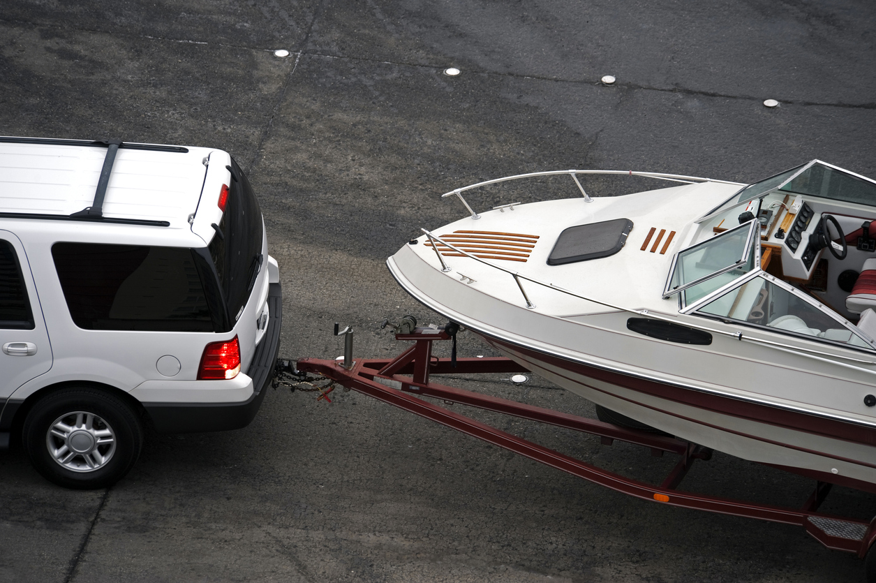 Boat on a trailer being towed by an SUV