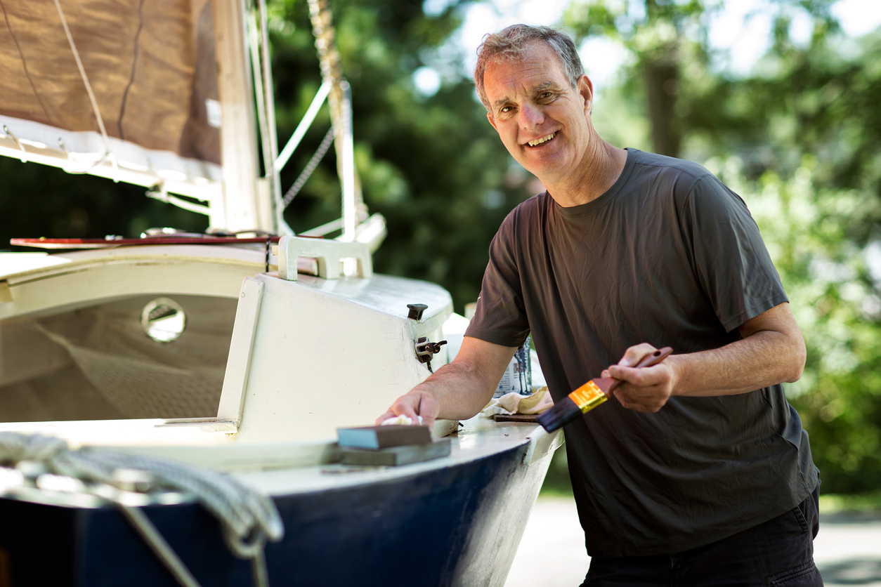Man de-winterizing a boat with fresh coat of paint