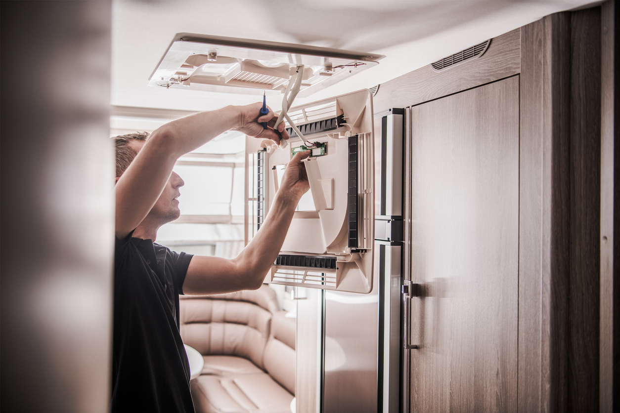 Owner inspecting his RV's air conditioning system