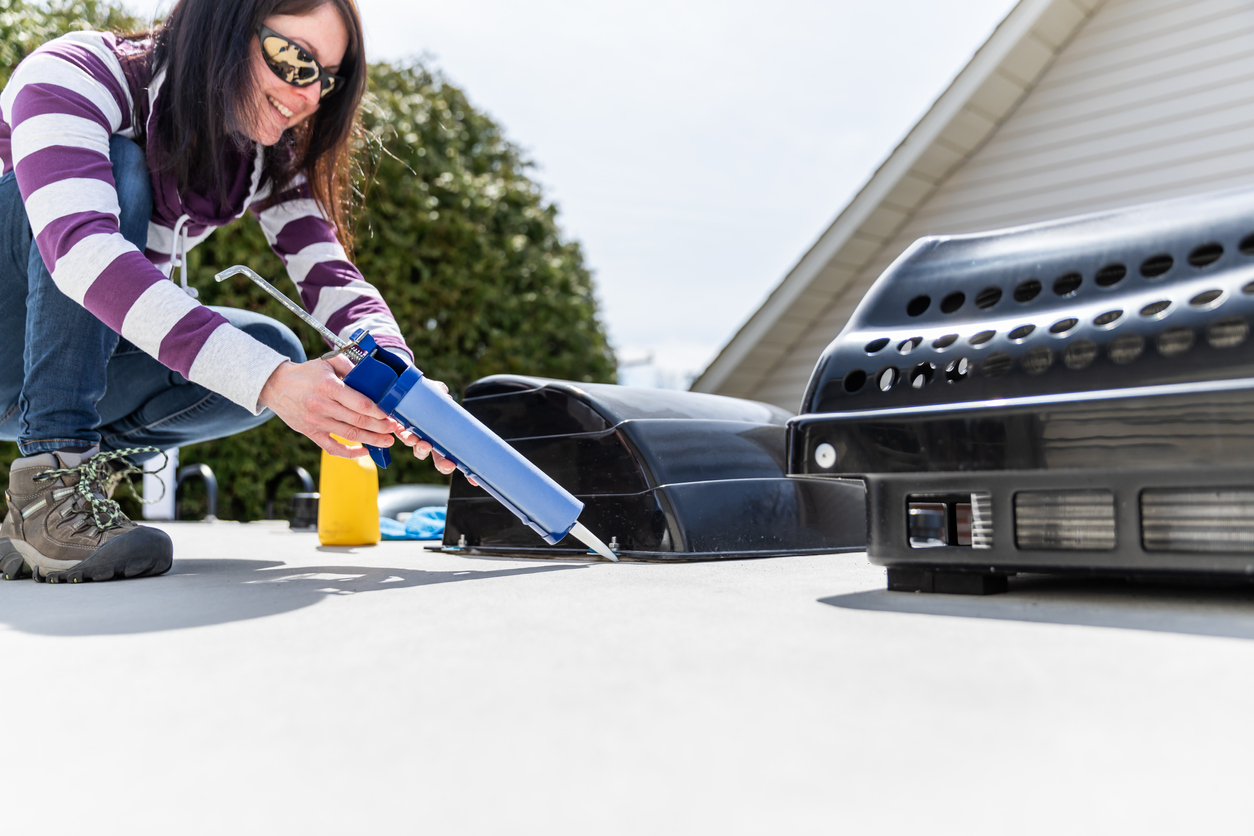 Owner sealing up potential leaks as part of her RV maintenance checklist