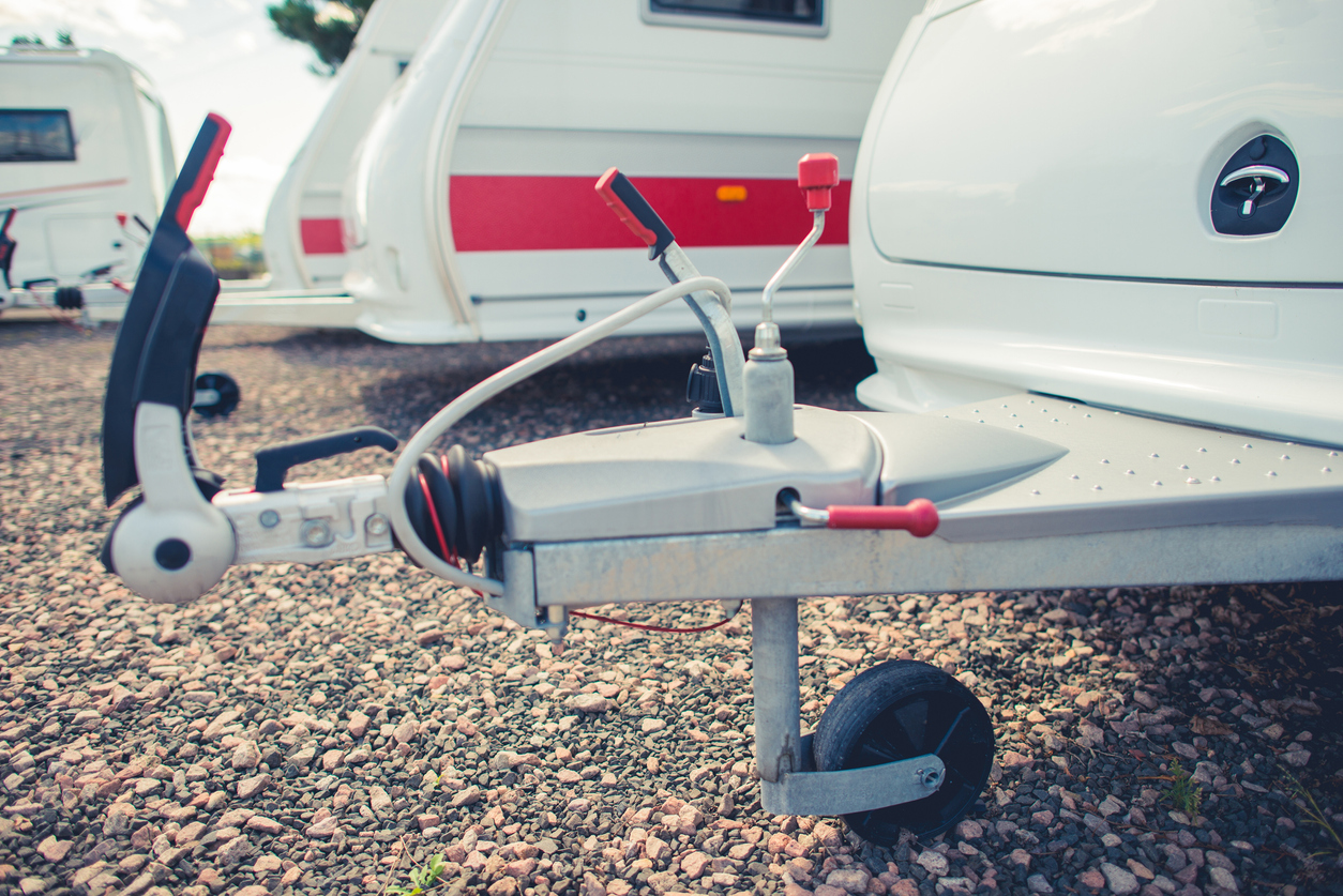 Close-up of an RV trailer hitch in a gravel-covered lot