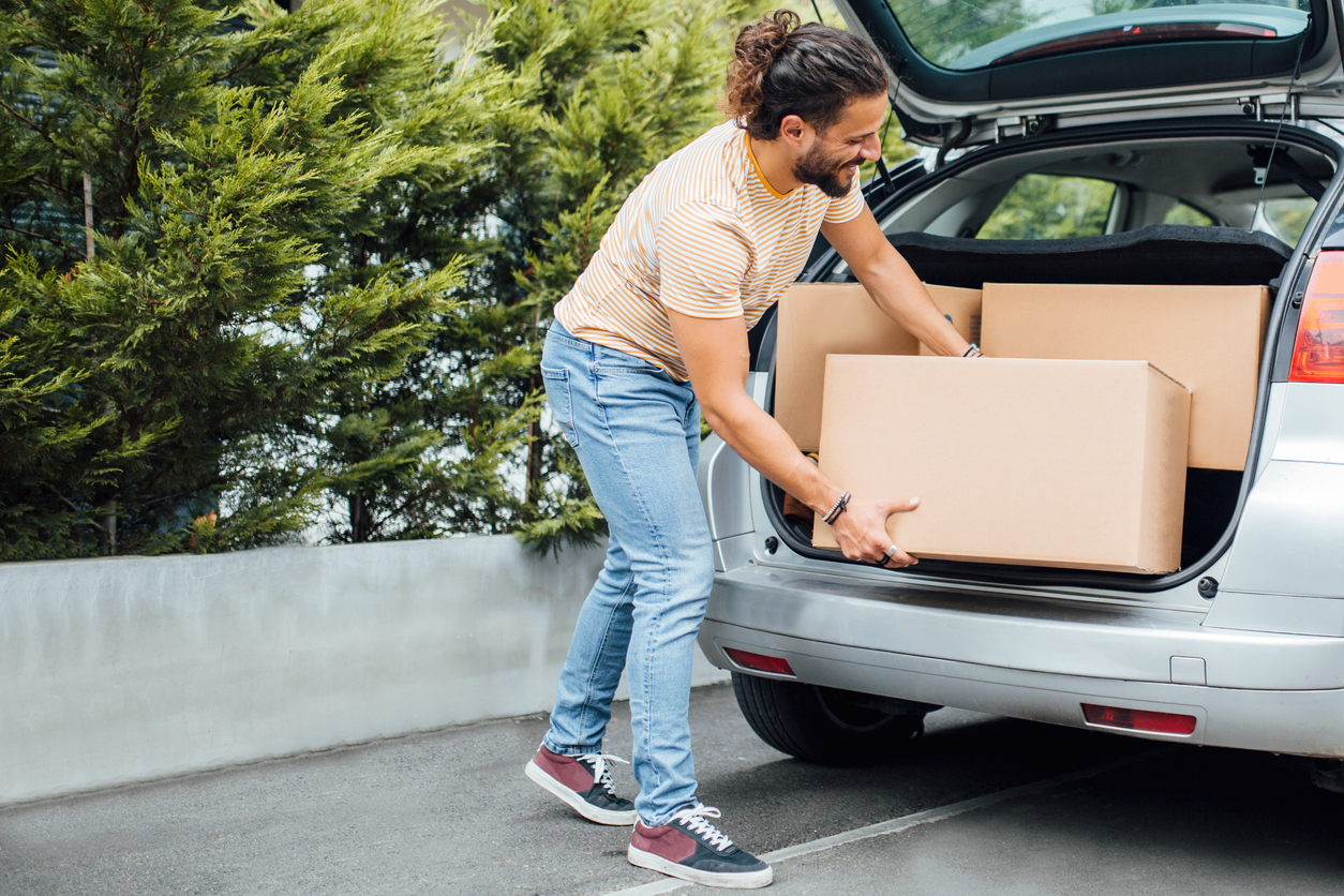 Man packing boxes into the back of his car