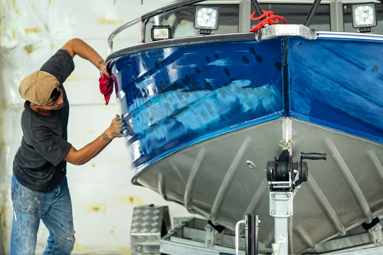 Boat owner performing seasonal cleaning and maintenance on the hull
