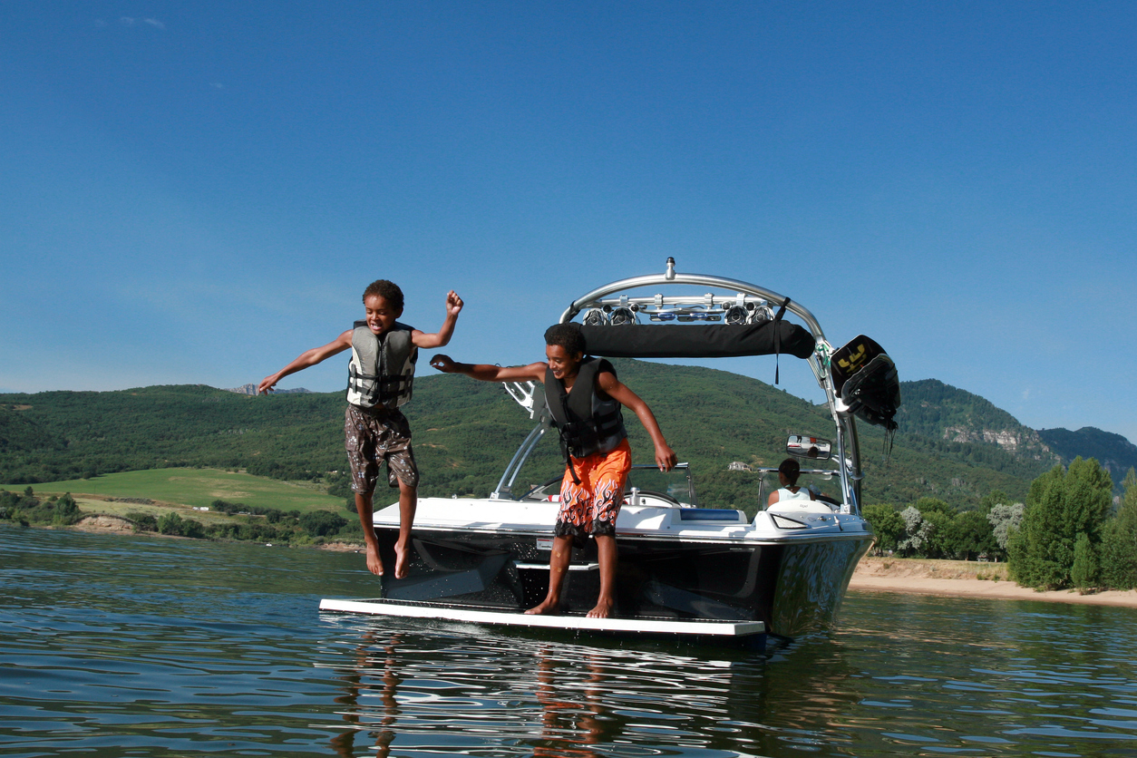 Children in life vests jumping from a boat into the water