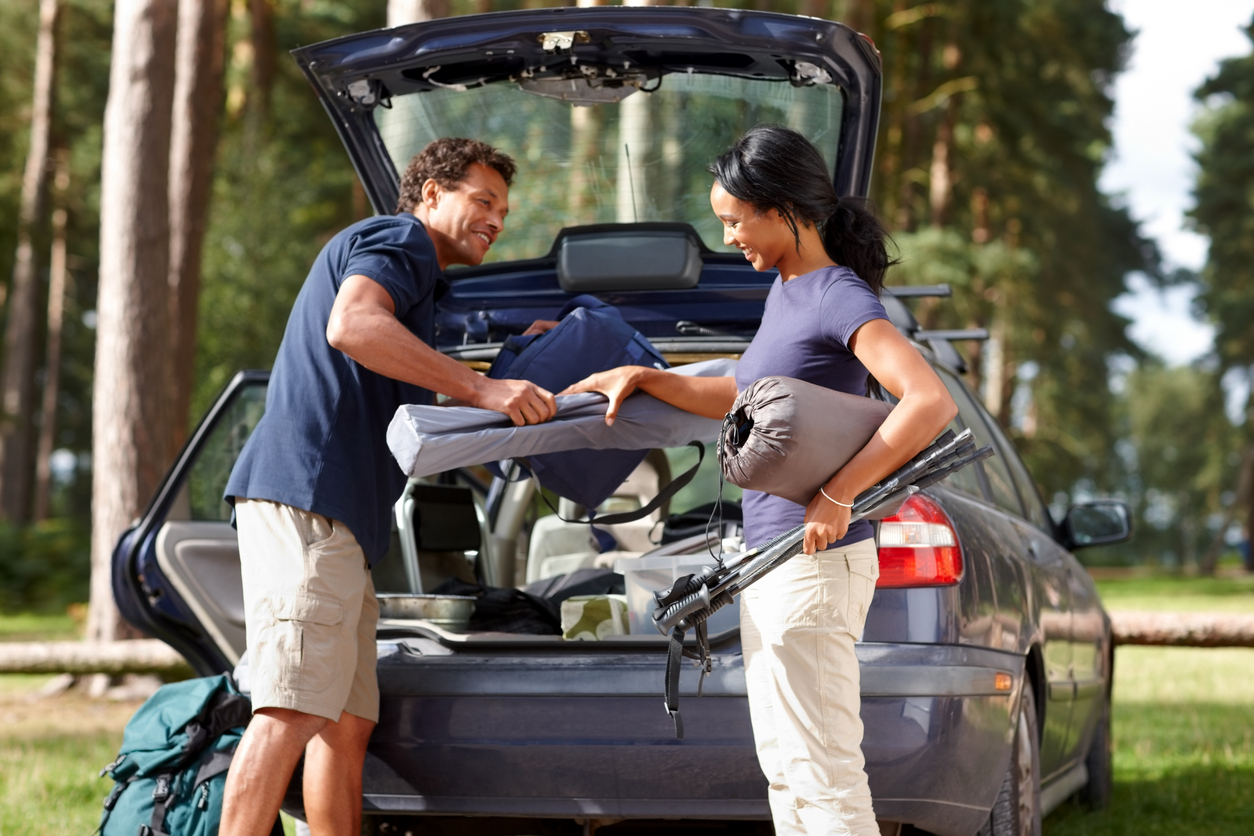 Couple unpacking organized camping gear from a car